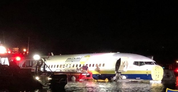 Passenger jet slips on a US airport runway in the river